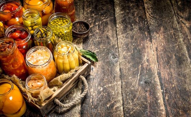 Différents légumes en conserve de légumes et champignons dans des bocaux en verre sur table en bois.