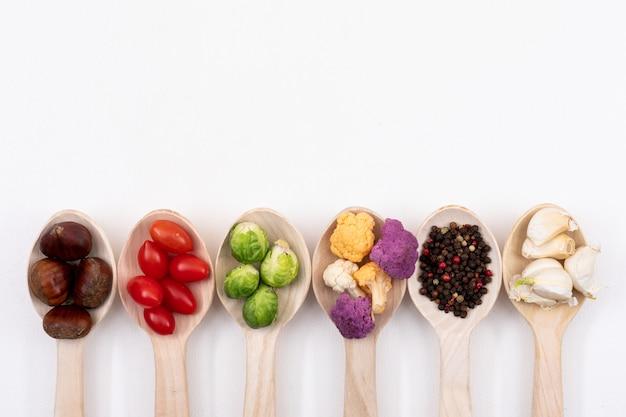 Différents légumes sur des cuillères en bois