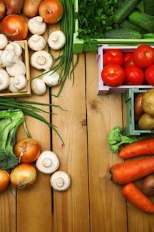 Différents légumes dans des boîtes sur la vue de dessus en bois