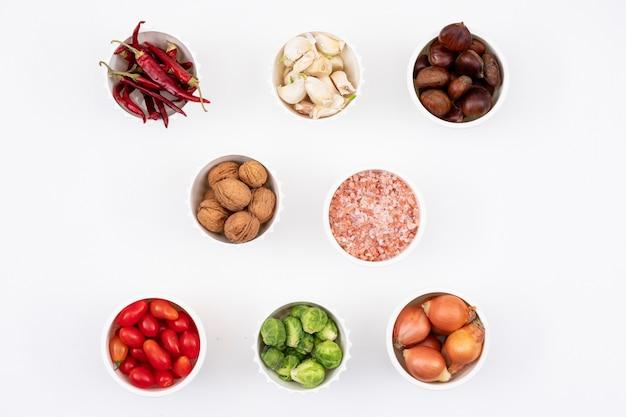 Différents légumes dans un petit bol blanc sur blanc