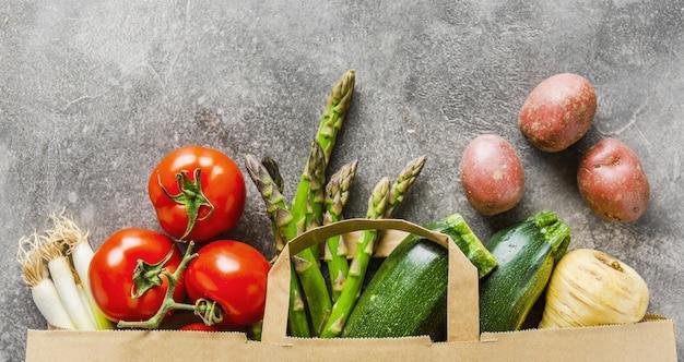Différents légumes dans un sac en papier sur fond gris