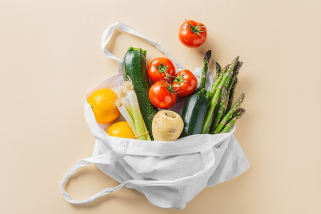 Différents légumes dans un sac en textile sur beige