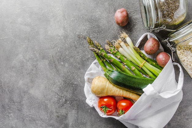 Différents légumes dans un sac en textile sur fond gris