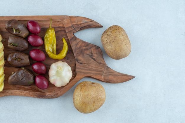 Différents légumes fermentés sur une planche, sur le marbre.