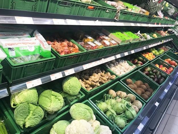 Différents légumes frais dans des boîtes sur les étagères des supermarchés