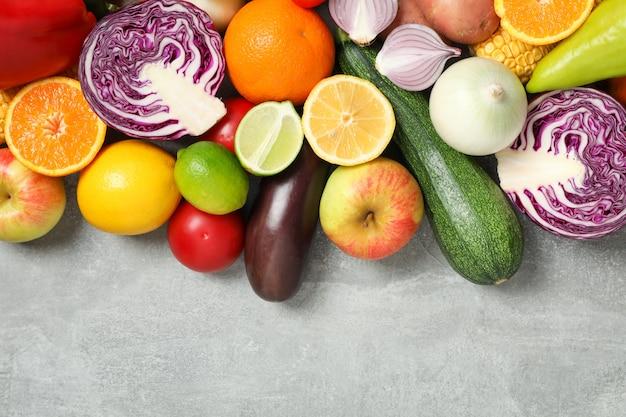 Différents légumes et fruits sur une vue de dessus grise différents légumes et fruits sur une vue de dessus grise