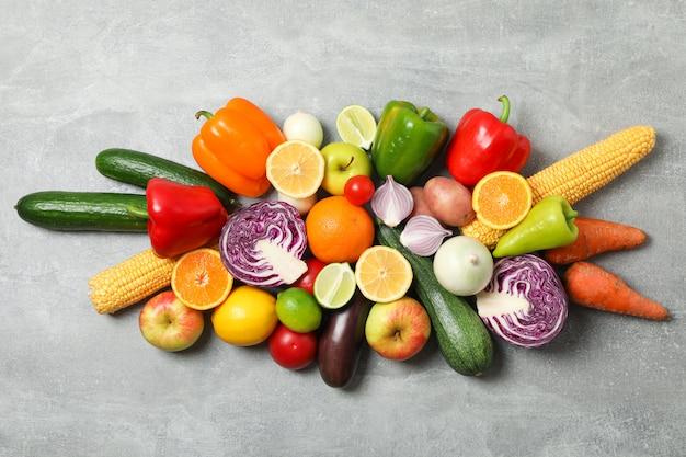 Différents légumes et fruits sur la vue de dessus grise