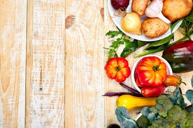 Différents légumes pour manger sainement sur fond de bois.