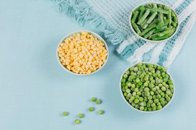 Différents légumes surgelés bio sur fond bleu clair. haricots verts, pois et maïs sucré dans un bol