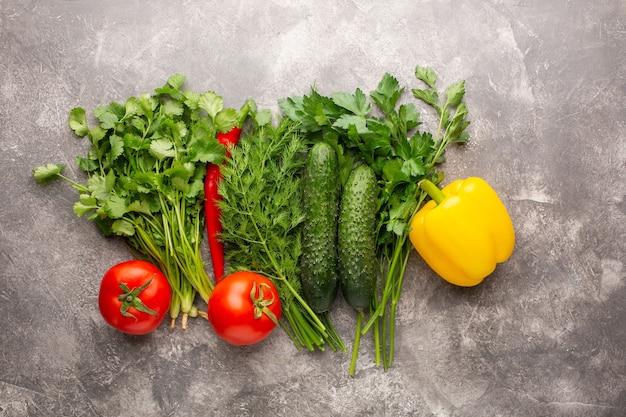 Différents légumes verts frais, tomates, concombre, poivron et piment sur une surface de béton gris