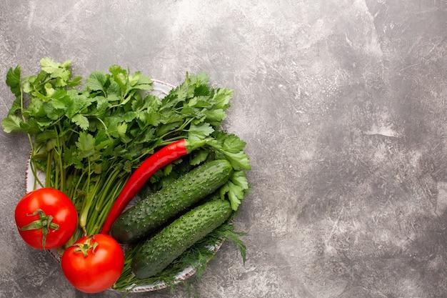 Différents légumes verts frais, tomates et piments sur une assiette ronde