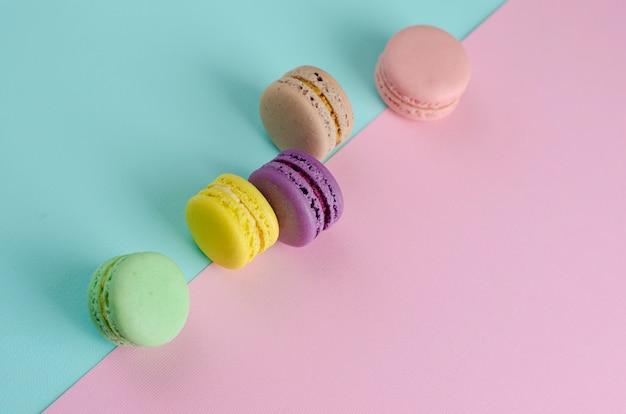 Différents macarons de biscuits colorés sur des couleurs pastel colorées