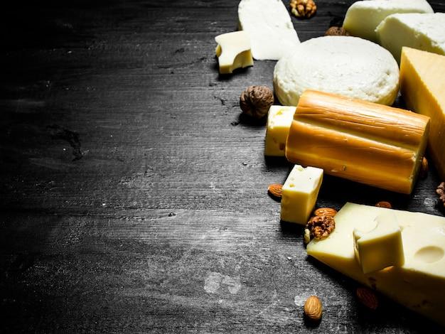 Différents morceaux de fromage avec des noix sur une table en bois noire.