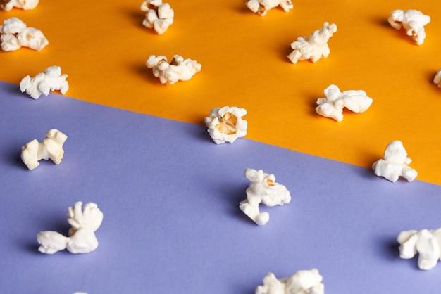 Différents morceaux de pop-corn savoureux sur demi-orange demi-violette. concept de film.