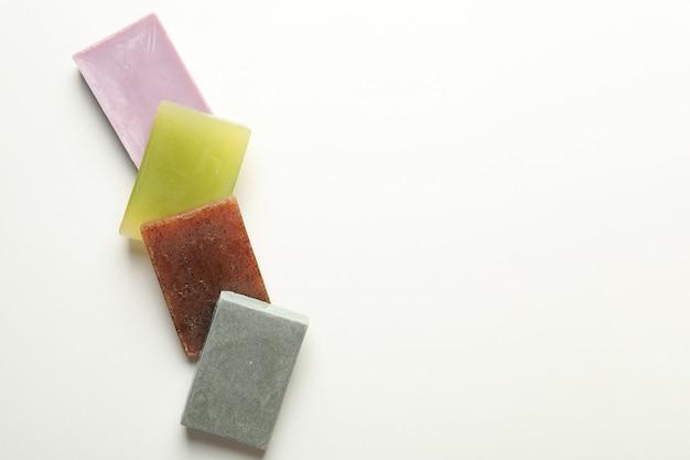 Différents morceaux de savon naturel sur fond blanc