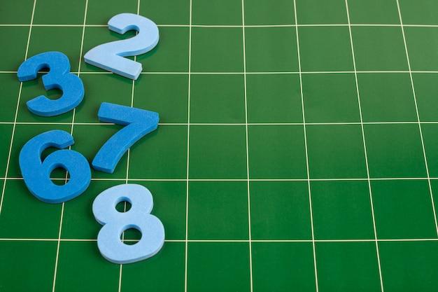 Différents nombres se trouvent sur la surface verte du tableau noir