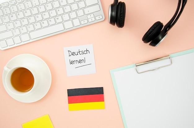 Différents objets d'apprentissage avec drapeau allemand sur fond de pêche