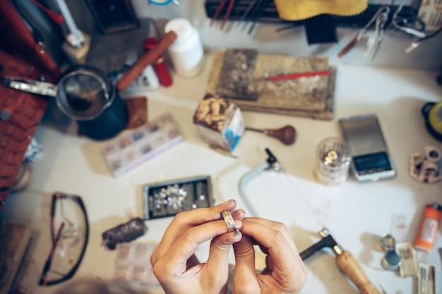 Différents outils d'orfèvres sur le lieu de travail des bijoux. bijoutier au travail en bijouterie. bureau pour la fabrication de bijoux artisanaux avec des outils professionnels. vue rapprochée des outils.
