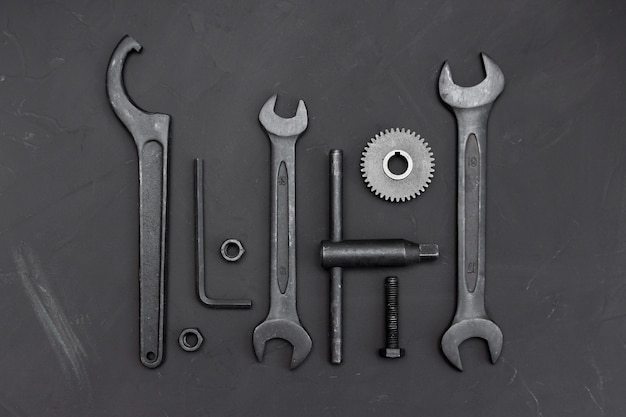 Différents outils sur une table sombre. clé, outils, roues dentées, clés polygonales, clés à molette, roues dentées, vis et boulons.