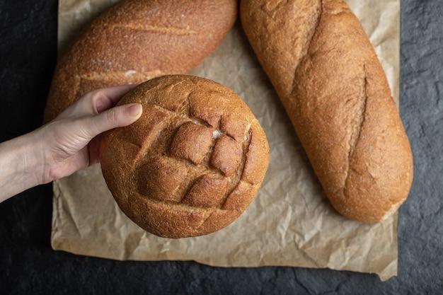 Différents pains de pain. femme tenant avec la main.