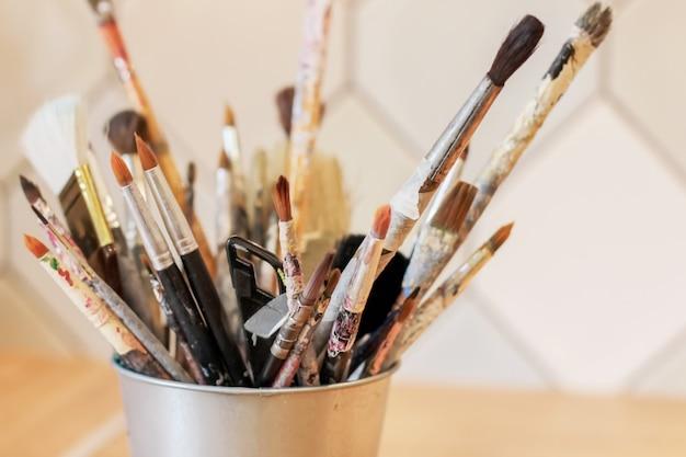 Différents pinceaux de l'artiste dans un seau en métal, mise au point sélective