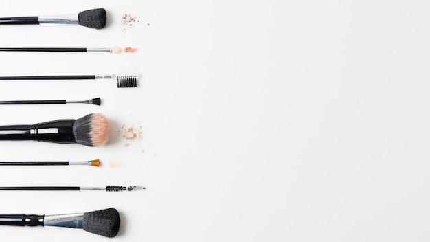 Différents pinceaux cosmétiques disposés sur fond blanc