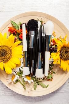 Différents pinceaux de maquillage sur plaque à côté de fleurs sauvages sur fond de bois