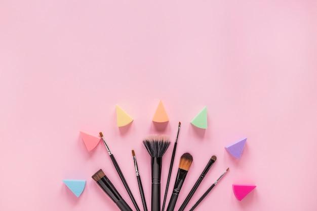 Différents pinceaux de poudre avec ombres à paupières sur la table rose
