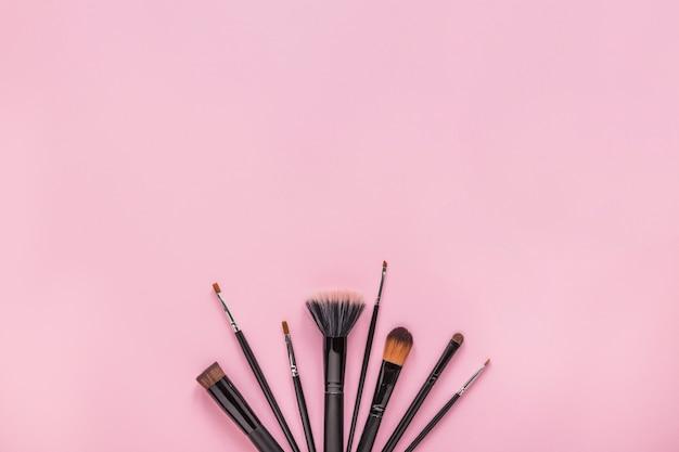 Différents pinceaux de poudre sur la table rose