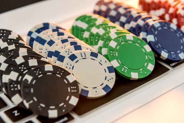 Différents prix des jetons de casino s'empilant sur un ordinateur portable