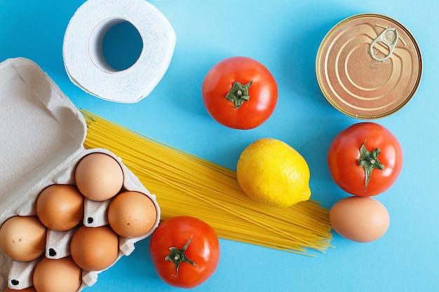 Différents produits alimentaires sains sur fond bleu. vue de dessus. boutique en ligne de fruits, légumes, œufs et épicerie.votre texte