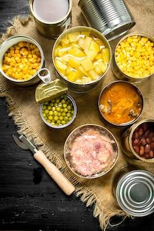Différents produits en conserve dans des boîtes de conserve. sur le tableau noir.