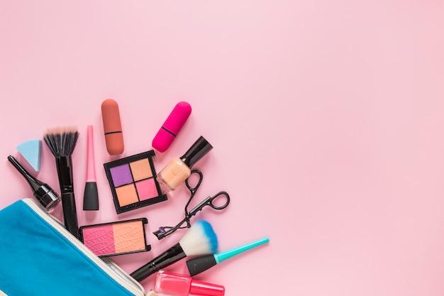 Différents produits cosmétiques dispersés dans un sac de beauté bleu