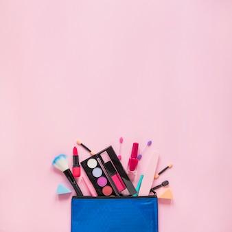 Différents produits cosmétiques dispersés dans un sac de beauté