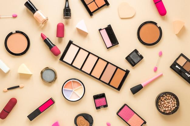 Différents produits cosmétiques dispersés sur une table beige