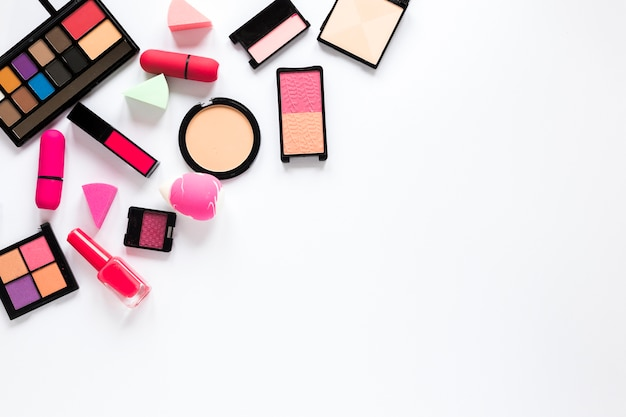 Différents produits cosmétiques dispersés sur une table blanche