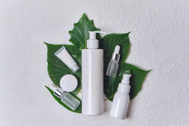 Différents produits cosmétiques de soins de la peau sur des feuilles vertes sur fond blanc, vue de dessus
