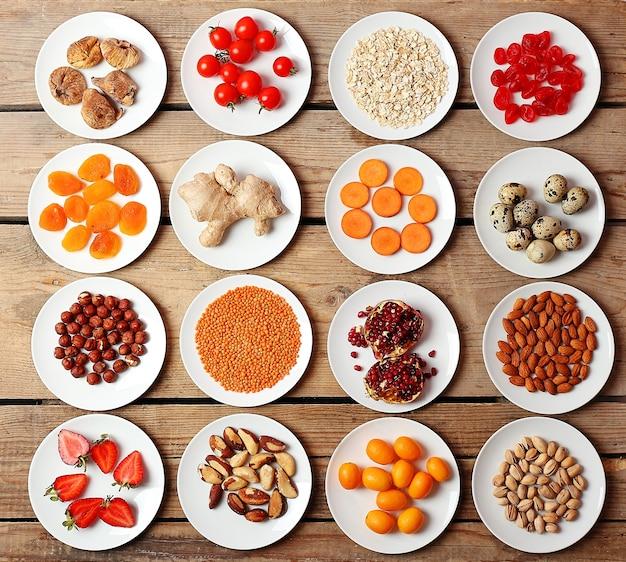 Différents produits sur des soucoupes sur table en bois, vue de dessus