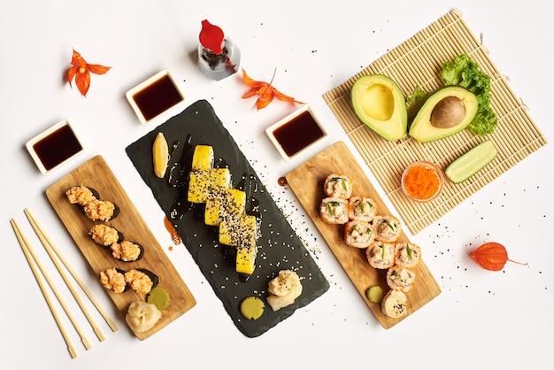 Différents rouleaux de sushi accompagnés de sauce soja et de wasabi.