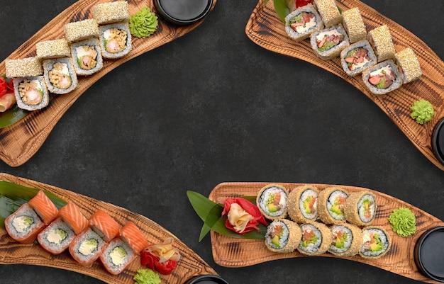 Différents rouleaux de sushi sur fond noir