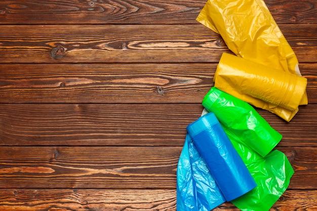 Différents sacs en plastique sur bois.