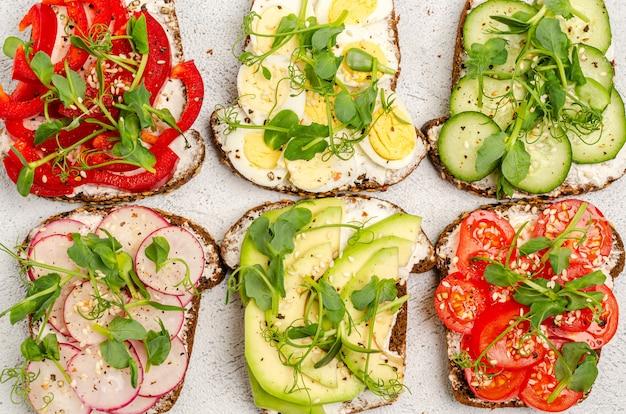 Différents sandwichs aux légumes et microgreens sur pain grillé