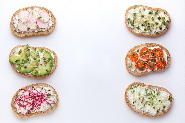 Différents sandwichs avec du pain aux céréales, des légumes et des micro-verts sur fond blanc
