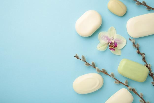 Différents savons blancs avec des fleurs. beaucoup de savon solide pour l'hygiène et la propreté sur fond bleu. vue de dessus.