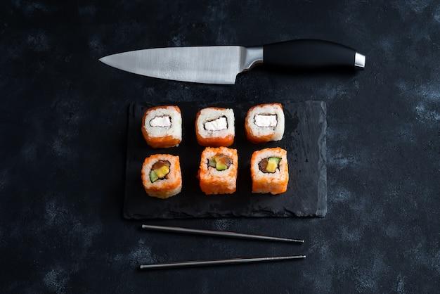 Différents sushis servis sur une assiette en ardoise noire avec un couteau japonais et des baguettes en métal