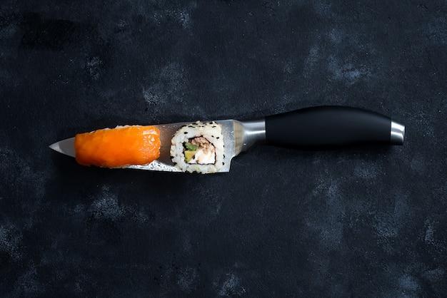 Différents sushis servis sur un couteau japonais sur fond noir.