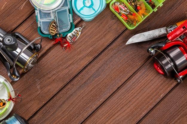Différents tacles de pêche avec leurres et moulinets sur fond brun en bois avec place pour le texte. conception pour la publicité et l'édition.