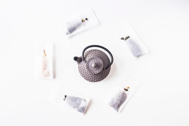 Différents thés dans des sacs filtrants jetables pour une infusion à côté d'une bouilloire en fonte grise