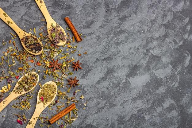 Différents thés secs en ligne de cuillères en bois