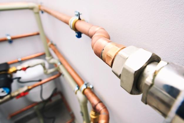 Différents tuyaux en cuivre et en plastique et autres vannes dans la chaufferie